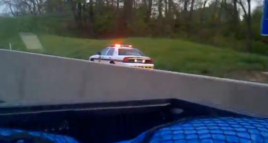 Cop drives backwards into highway traffic at full speed. But why?