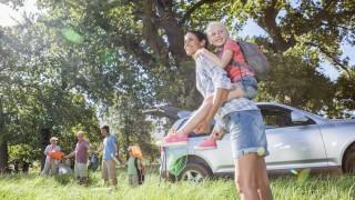 family unpacking a vehicle outside