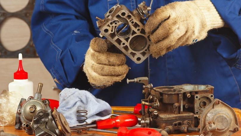Mechanic repairing old car engine carburetor