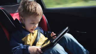 Child in the car with tablet