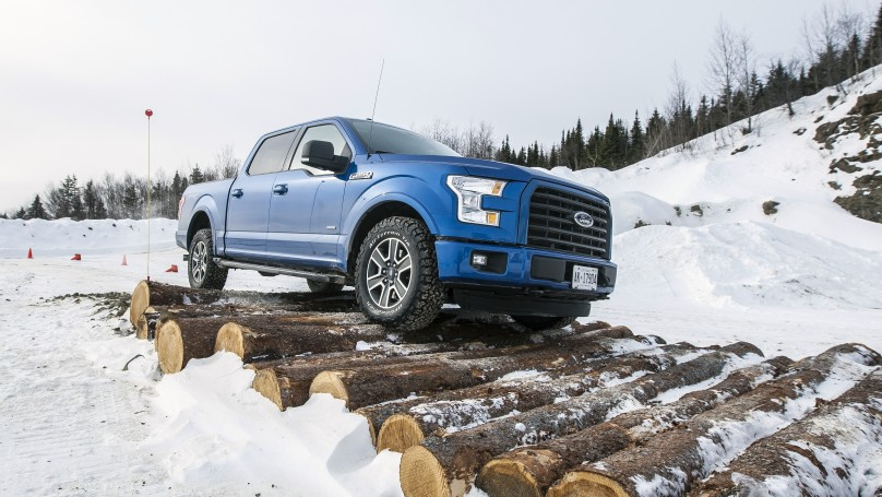 Ford F-150 driving over logs