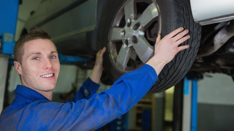 Male mechanic working on wheel of car