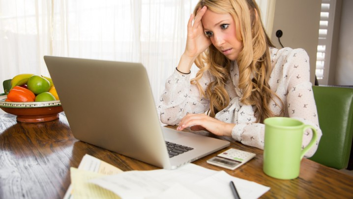 Frustrated woman doing her taxes at her home computer