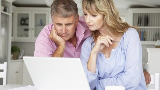 Mid age couple working at home on laptop
