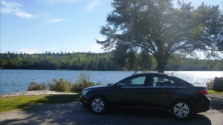 car in front of lake